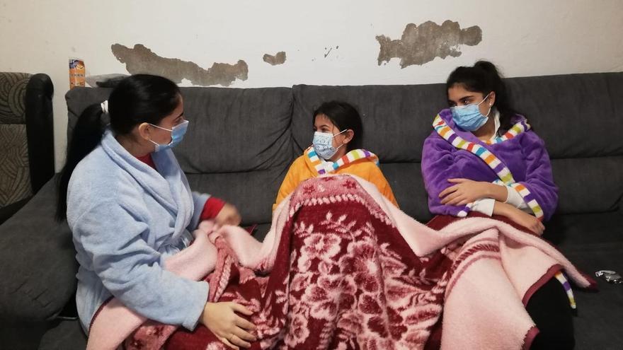 Emília amb les seues dues filles tapades amb mantes.