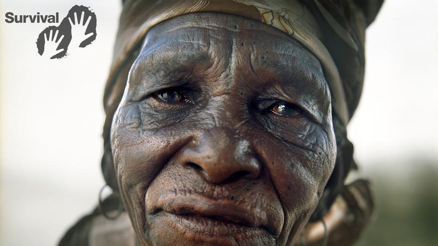 """Los bosquimanos son el pueblo originario del sur de África.  Entre 1997 y 2002 casi todos los bosquimanos fueron expulsados de sus hogares en la Reserva de Caza del Kalahari Central (CKGR, según sus siglas en inglés) y conducidos a campos de reasentamiento fuera de la reserva, donde no solo se les niegan sus medios de vida, sino que son humillados por actitudes racistas endémicas. Que nos llamen primitivos. Que nos llamen gente de la Edad de Piedra. Nuestro modo de vida nos viene bien. Hemos visto el desarrollo, y no nos gusta, dijo una mujer bosquimana. Xlarema Phuti, una curadora bosquimana, fue expulsada a la fuerza de Molapo, su hogar ancestral en la reserva, por el Gobierno y trasladada a Nuevo Xade, un campo de reasentamiento gubernamental conocido como el """"lugar de la muerte"""". Xlarema habló con Survival International sobre los poderes curativos de la tradicional danza del trance de los bosquimanos y sobre la tristeza que ha experimentado desde que los bosquimanos fueron expulsados de sus tierras. Cuando estoy bailando en la danza del trance, hablo con los ancestros para que me ayuden a curar al enfermo, dijo./ ©Dominick Tyler"""