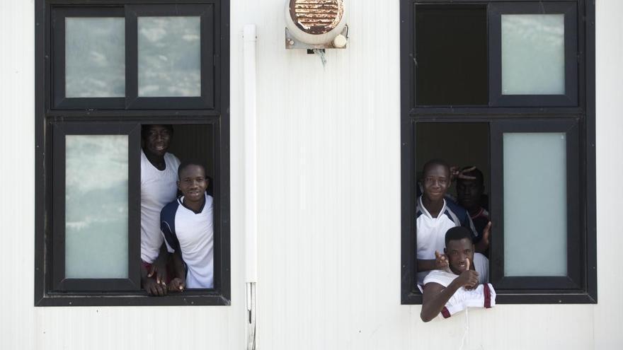 Cuatro jóvenes miran desde las ventanas