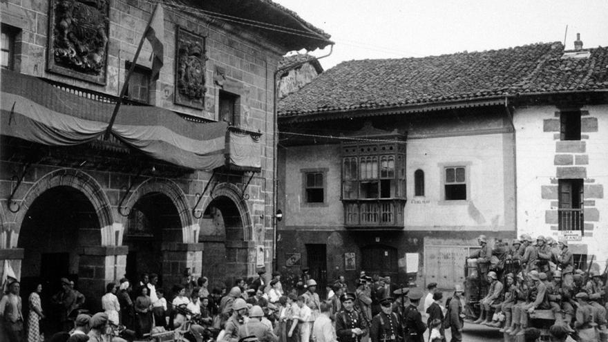 Las Brigadas de Navarra en Otxandio hacia el 6-7 de abril de 1937. Guardias de asalto y civiles procedentes de Vitoria (abajo, en el centro de la imagen) son los encargados de la seguridad; véase el ayuntamiento engalanado para la ocasión (Biblioteca Nacional).
