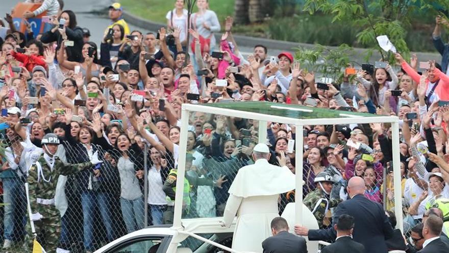 El papa Francisco (c) saluda a la multitud que lo aclama a su paso por una calle de Medellín (Colombia).