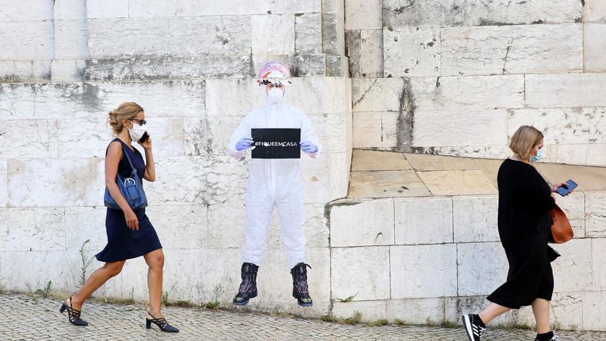 Dos mujeres con mascarilla pasan frente a un mural de un sanitario con un cartel de 'Stay home' en Lisboa.
