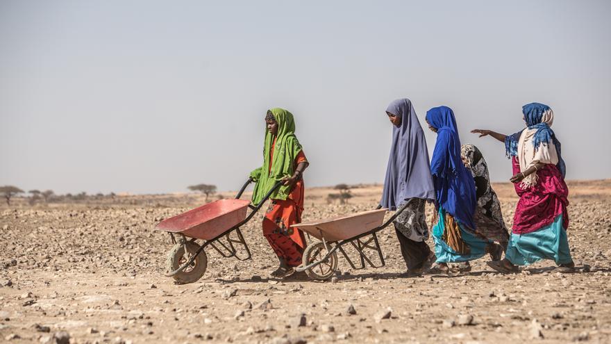 Un grupo de mujeres desplazadas por la sequía cargan bidones para ser rellenados de agua. Foto: Pablo Tosco / Oxfam Intermón