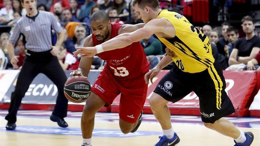 El escolta estadounidense del Zaragoza Gary Neal intenta avanzar con el balón ante la oposición del jugador polaco del Tenerife Mateusz Ponitka.. EFE/JAVIER BELVER