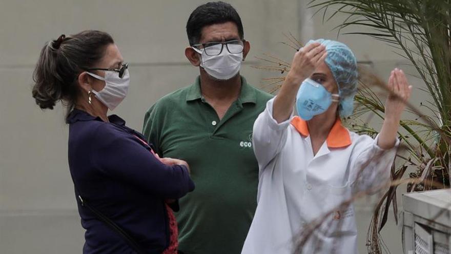 Zilmar Bezerra de Azevedo (i), de 58 años, y su esposo Francisco de Azevedo (c) conversan con una doctora después de que una prueba de coronavirus aplicada a Francisco haya resultado positivo, este viernes en Niterói, ciudad vecina a Río de Janeiro (Brasil).