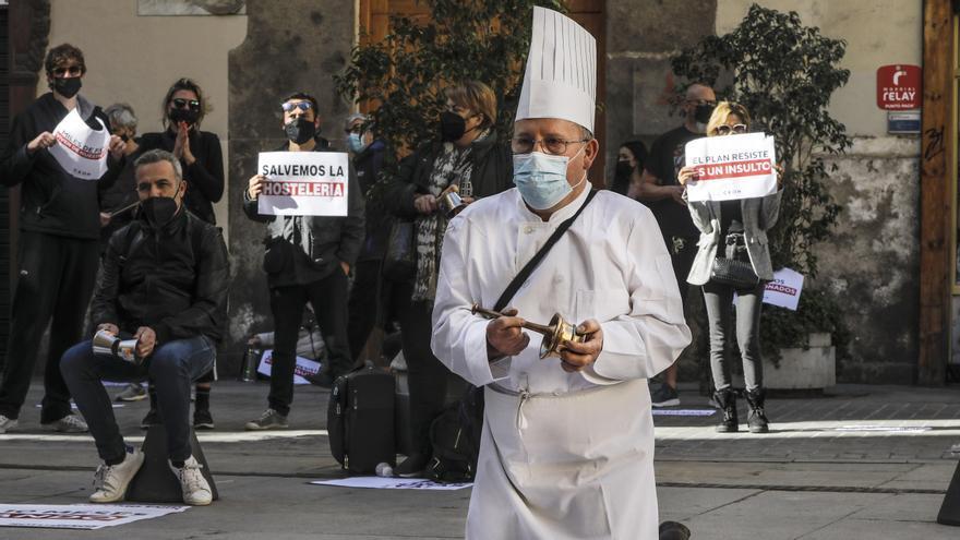 Un hombre con uniforme de cocinero se arrodilla durante una manifestación de hosteleros valencianos frente a las puertas del Palau de la Generalitat