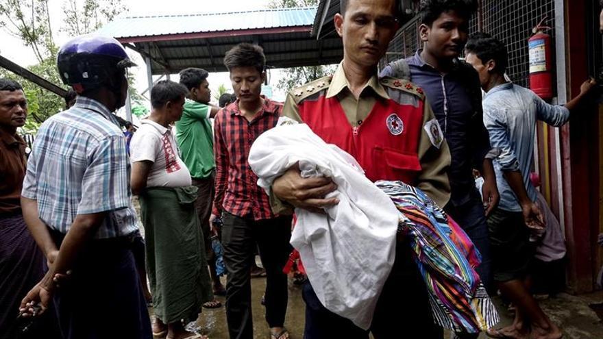Imagen de archivo. Un voluntario de la Cruz Roja lleva a un niño junto con mujeres desplazadas rohinyás del área de Maungdaw.