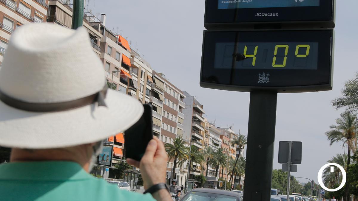 Un viandante fotografía un termómetro urbano