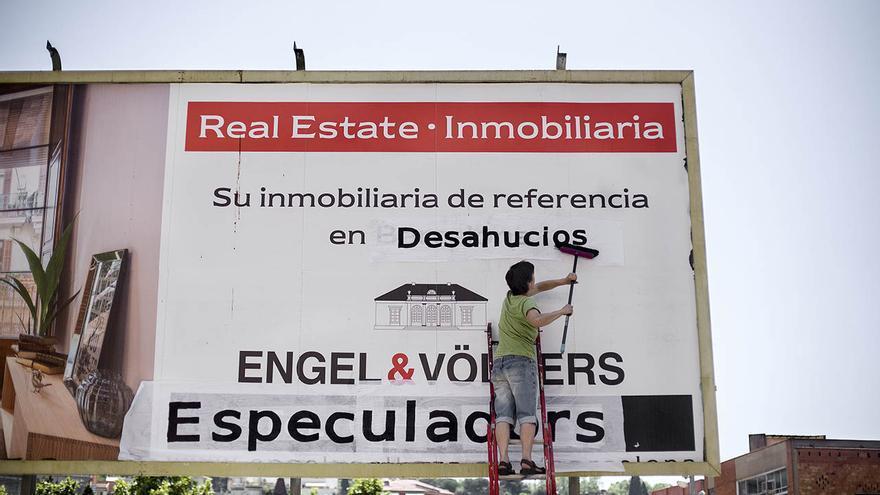 Una activista empapela un cartel de una inmobiliaria durante la manifestación en contra del aumento del precio del alquiler