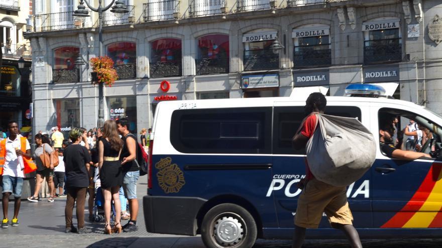 Vendedor del top manta marchándose del lugar donde estaba vendiendo en la calle por la presencia de la policía   FOTO: P.R.
