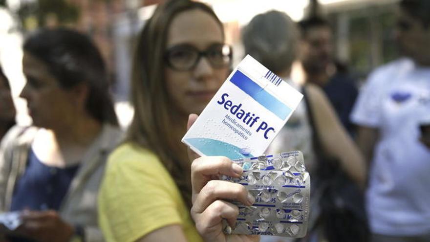 Una activista muestra uno de los fármacos que se vendía de forma irregular en España