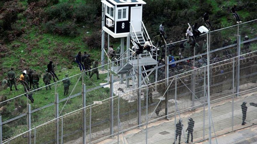 Imagen de archivo de varios migrantes encaramados a la valle de Ceuta.