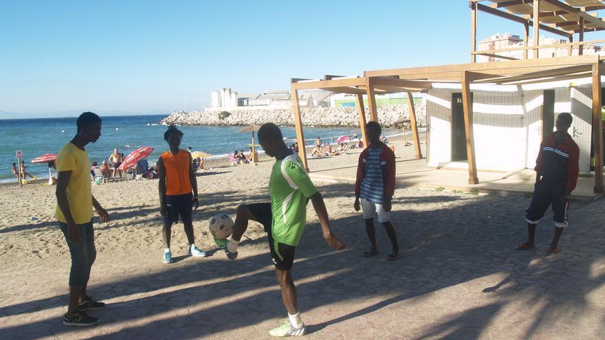 Varios migrantes juegan en la playa Benítez de Ceuta.