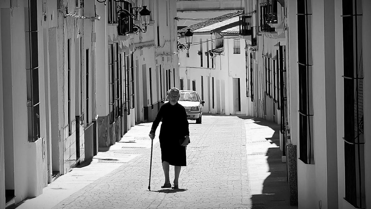 Una señora pasea por un pueblo de Extremadura.