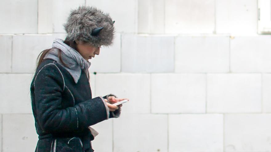 Una mujer anda por la calle mientras usa su teléfono móvil