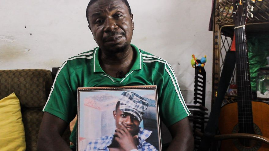El padre de Bikai Luc Firmin, una de las víctimas de las muertes de Ceuta,  sostiene una fotografía suya en Camerún, donde reside.