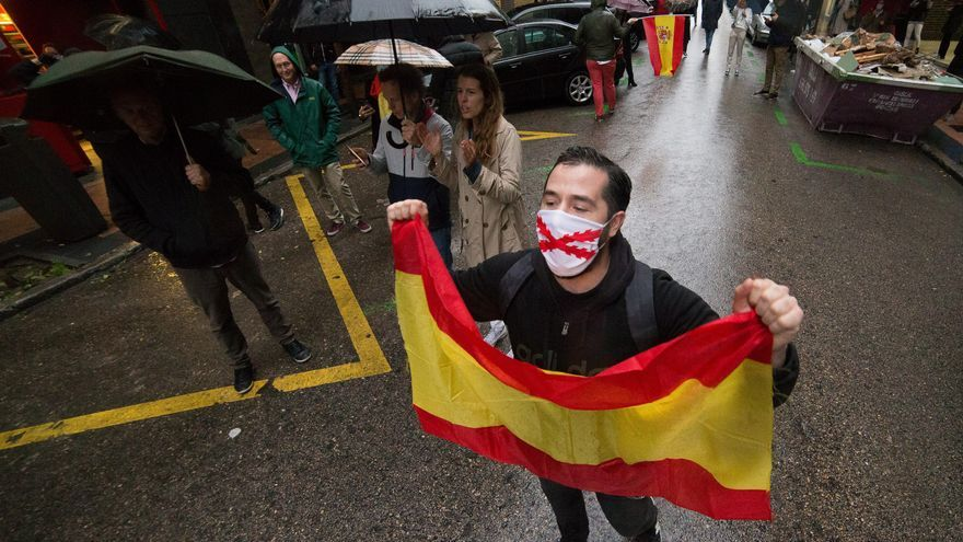 Un hombre con mascarilla levanta una bandera de España en señal de protesta durante la concentración de los vecinos del barrio madrileño de Salamanca en la calle Núñez de Balboa por la gestión del Gobierno contra el coronavirus. En Madrid, España, a 12 de mayo de 2020.