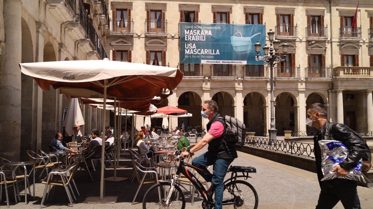 Un hombre pasea con mascarilla, con un cartel de la campaña de Vitoria para fomentar su uso al fondo