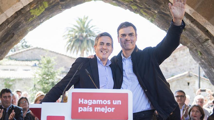 Pedro Sánchez y Pablo Zuloaga saludando a los asistentes al acto sobre municipalismo celebrado en Cartes.