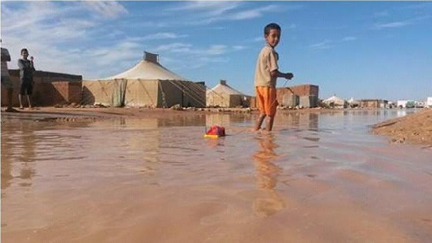 En la imagen, un niño en medio del agua caída en los campamentos.