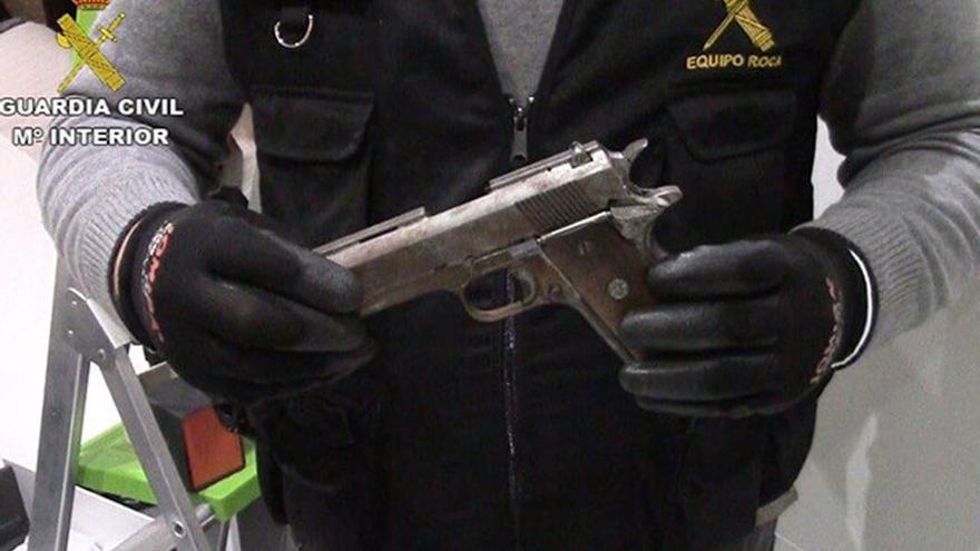 Un guardia civil muestra una de las armas incautadas.