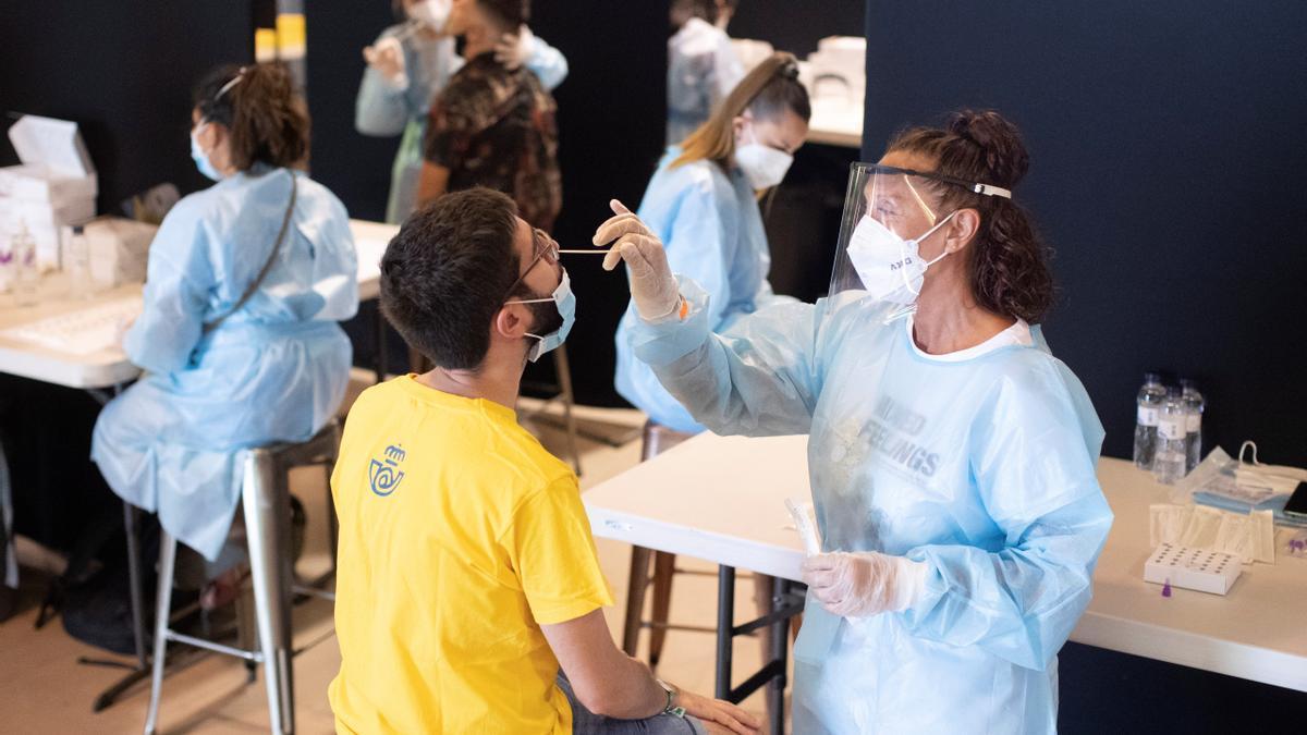 Una sanitaria realizando una prueba PCR a un joven en Euskadi
