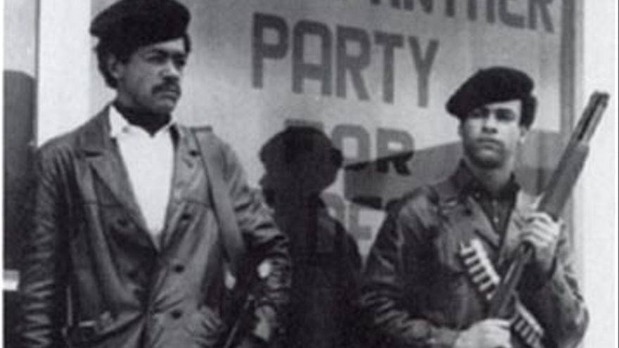 Black Panther Party founders Bobby Seale and Huey P. Newton standing in the street, armed with a Colt .45 and a shotgun.