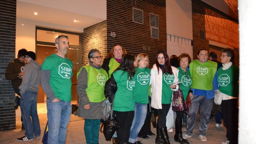 Varios activistas de la PAH en la puerta de un edificio ocupado por varias familias sin hogar en Castellón.