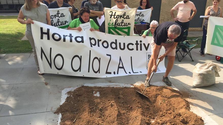 Los manifestantes ponen tierra para montar un pequeño huerto como protesta contra la ZAL