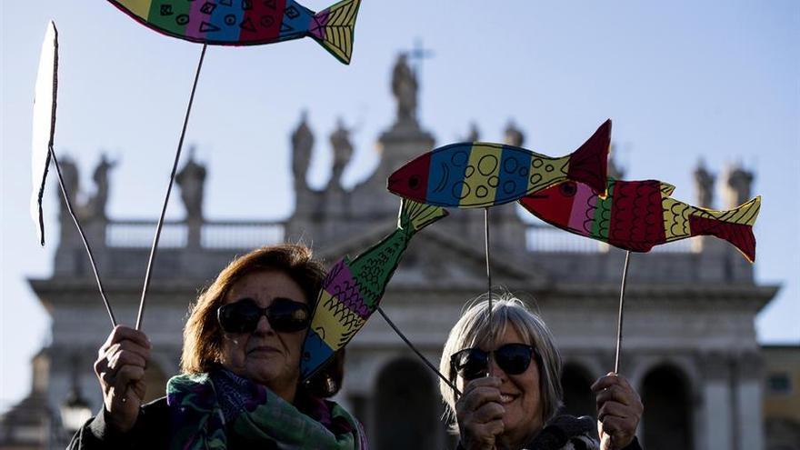 Dos mujeres portan en sus manos pancartas con forma de sardina