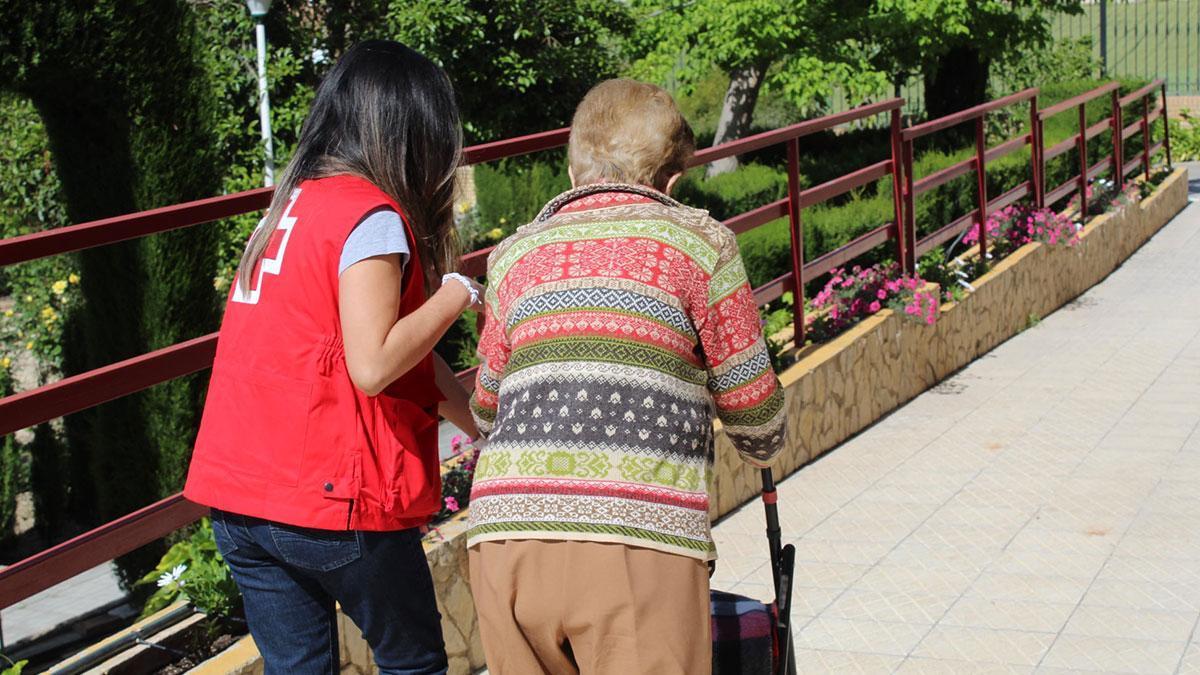 Una voluntaria de Cruz Roja acompañando a una persona mayor a vacunarse en Montilla.