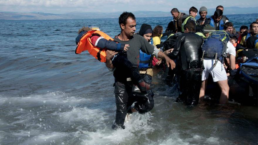 Un socorrista saca a un niño de la embarcación neumática en la que ha viajado con otros refugiados desde Turquía.
