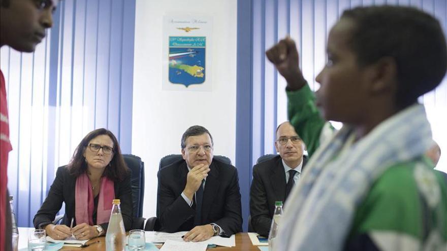 La comisaria europea de Interior, Cecilia Malmström, escucha a unos supervivientes del naufragio en Lampedusa.