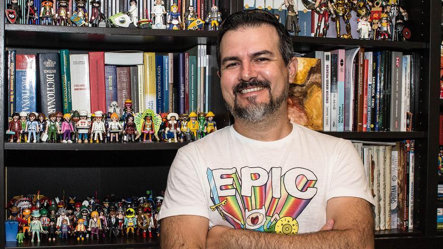 Carlos Lobato posa en su casa ante algunas de las cientos de figuras de Playmobil de su colección.