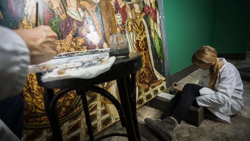 Elena Naval trabaja sobre la tabla de la Adoración de la Cruz de Blesa.