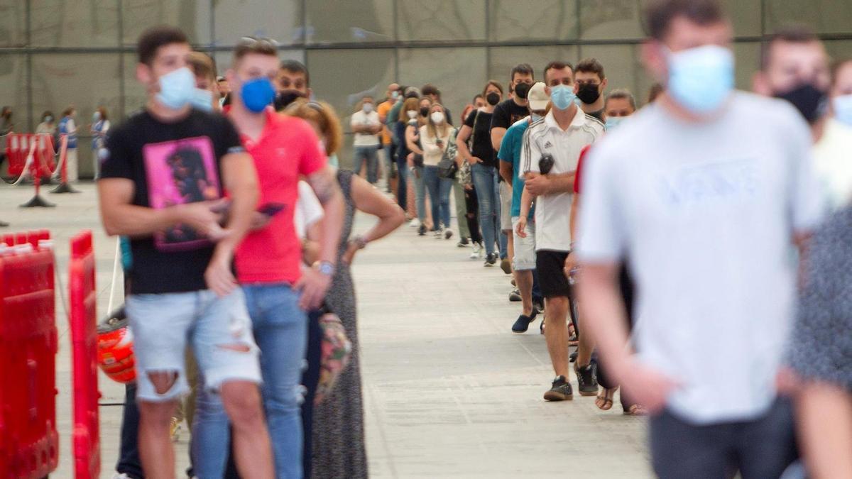 Decenas de jóvenes esperan su turno para ser vacunados en centro de vacunación en el Instituto Ferial de Vigo.