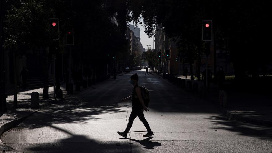 Un hombre con tapabocas es visto mientras camina por una calle semivacía en el centro de Santiago (Chile).