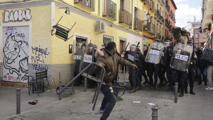 Un vecino lanza una silla contra los antidisturbios.