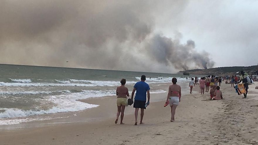 La playa de Matalascañas esta tarde, y el área del incendio, Mazagón y Moguer, al fondo