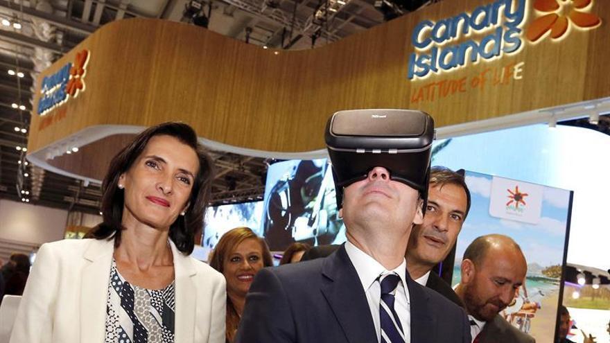 El presidente del Gobierno de Canarias, Fernando Clavijo (c), acompañado por la consejera de Turismo, María Teresa Lorenzo (i), prueba unas gafas de realidad virtual en el stand de la isla de Lanzarote