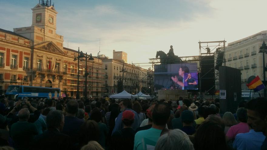 Asistentes de la concentración viendo el discurso de Pablo Iglesias