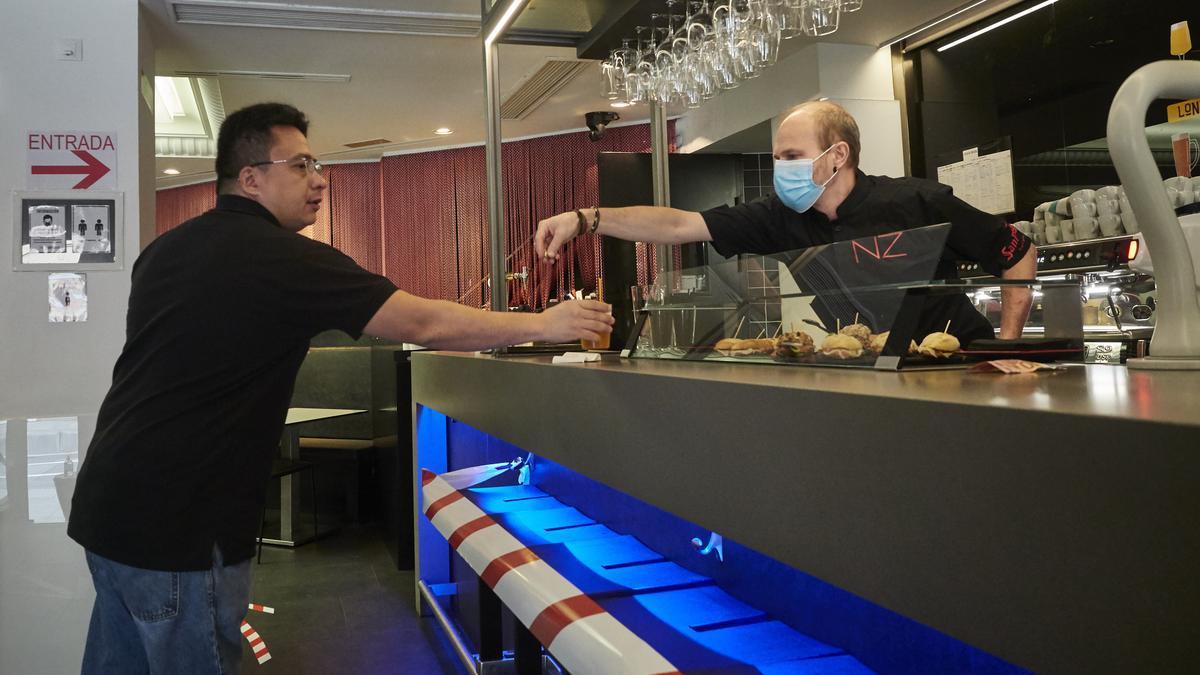 Un camarero en la barra de un bar.