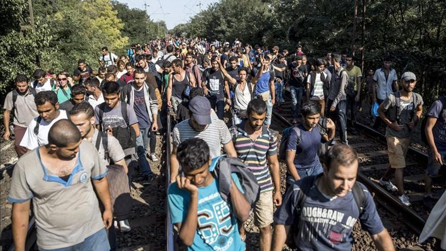 Centenares de refugiados, en marcha para alcanzar a pie la frontera con Austria.