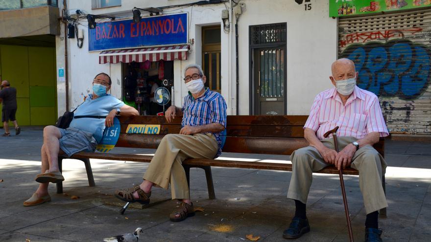 Antonio Ruiz (izquierda) y Joaquin Maneja (centro), guardan la distancia social en el barrio de La Torrassa de l'Hospitalet de Llobregat.