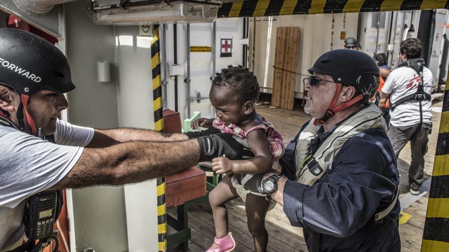 """Nael Nasser (de azul), mediador cultural a bordo del Bourbon Argos ayuda a una niña tras quitarle su pequeño salvavidas. """"En su desesperación, los padres y madres arrojan a sus hijos a nuestros brazos y confían ciegamente en unos extraños como nosotros para que los llevemos al barco de rescate. Resulta desgarrador ver cómo familias con niños de tan solo unos meses de edad en este tipo de situaciones límite"""" afirma Sebastian Stein, coordinador de MSF en el Argos. Fotografía: Francesco Zizola/NOOR"""