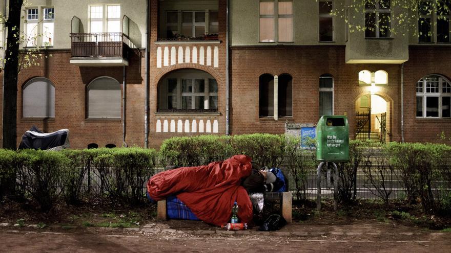 Imagen de archivo de una persona sin hogar tendida en el banco de un parque en Berlín.