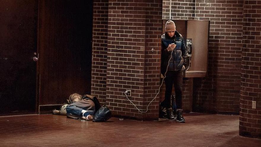 Una persona duerme en la calle mientras otra carga su móvil