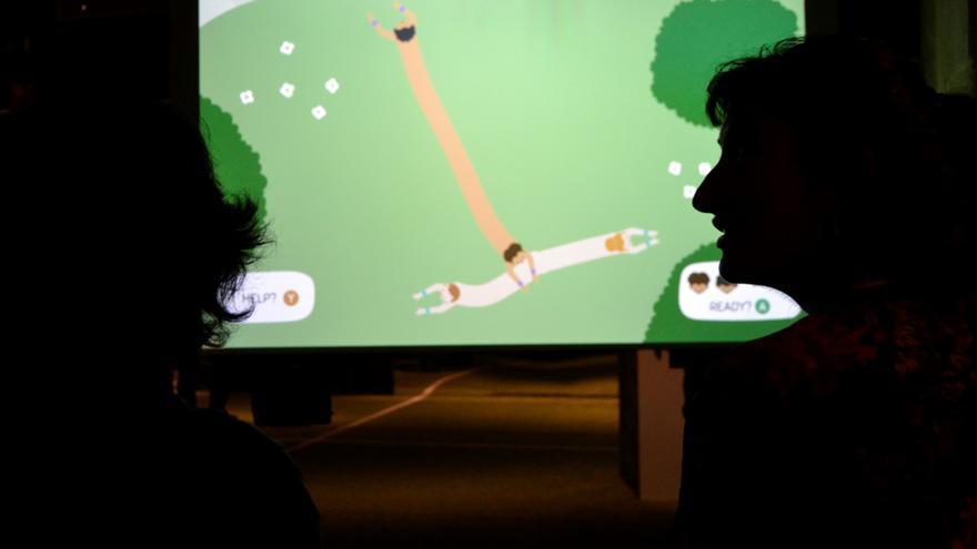 Dos visitantes a la exposición 'Gameplay' del CCCB, jugando al videojuego 'Push Me Pull You'
