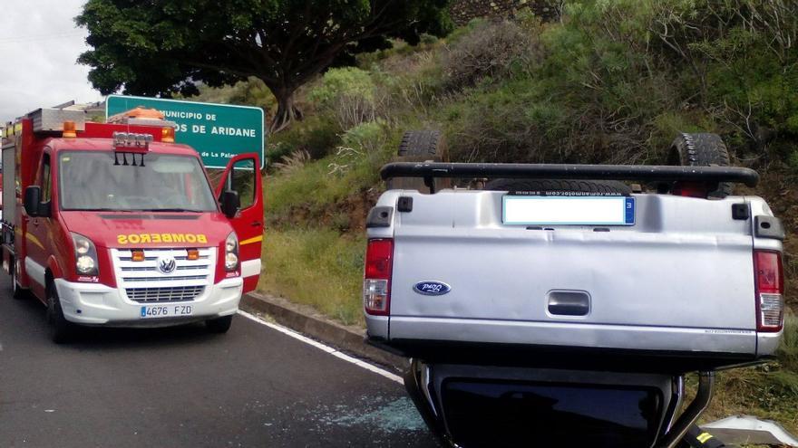 En la imagen, el turismo volcado y un vehículo de los bomberos. Foto: BOMBEROS LA PALMA