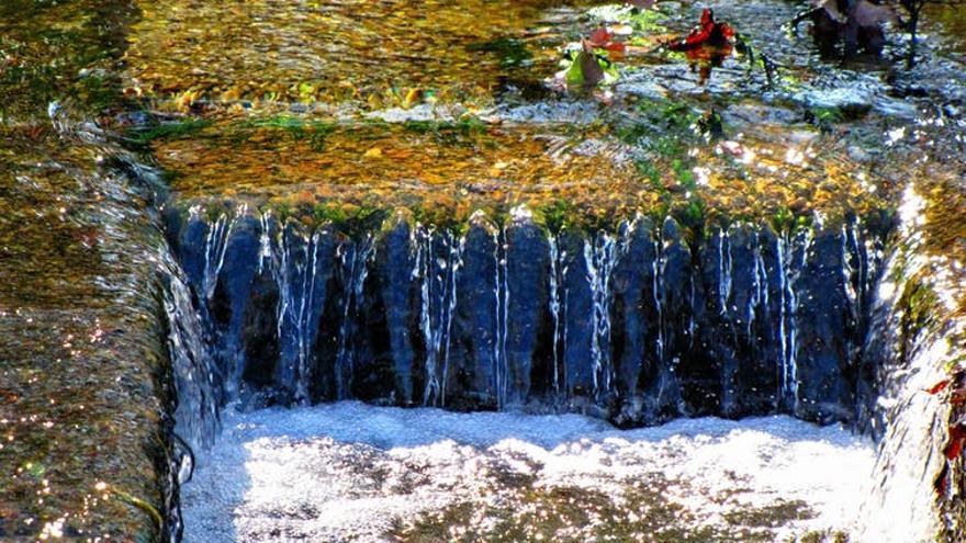 Corriente de agua que termina en una alcantarilla.